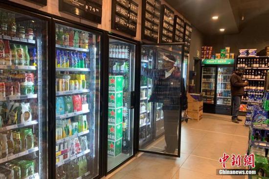 资料图:南非约翰内斯堡,一家酒类商店的店员佩戴面罩整理冰箱内的货物。 中新社记者 王曦 摄