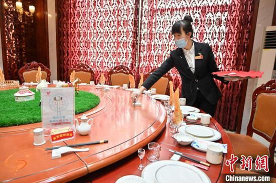 资料图:2021年1月13日,呼和浩特某酒店工作人员在餐桌上摆放公筷。刘文华 摄