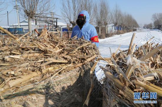 1月15日,在黑龙江省绥化市望奎县后三乡一村庄,志愿者在卡点前值班。新华社发(张涛 摄)