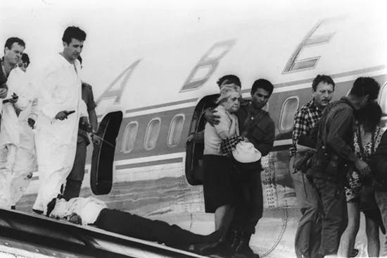 行动结束后,乘客走下飞机。