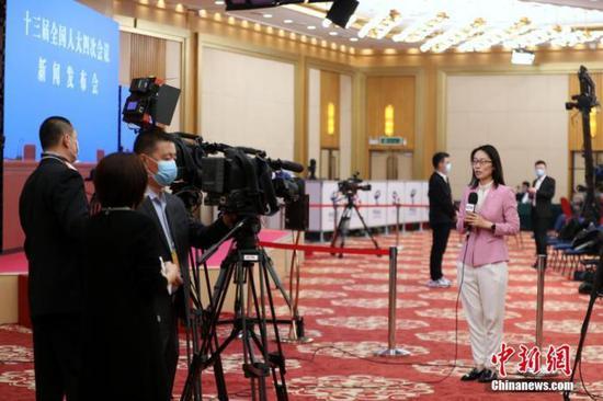 3月4日晚,十三届全国人大四次会议新闻发布会在北京人民大会堂新闻发布厅举行。图为新闻发布会开始前,央视记者在分会场梅地亚中心内进行直播。中新社记者 蒋启明 摄
