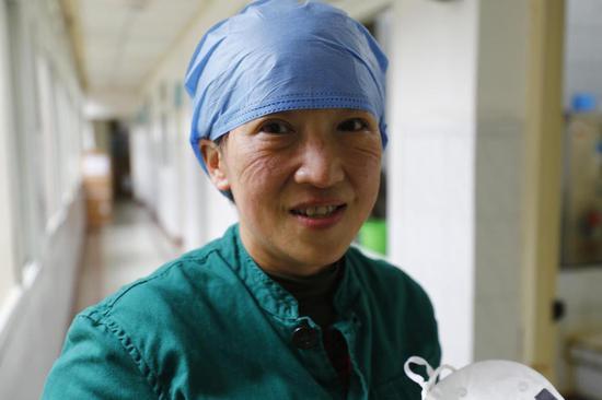 中部战区总医院党员、感染科主任医师江晓静抢救完病人后露出笑容(2020年2月15日摄)。 新华社发(王皓宇 摄)