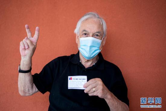 """2月12日,在智利南部河大区福德罗诺市的一处社区家庭保健中心,智利总统皮涅拉接种中国疫苗后比出""""V""""的手势。新华社发"""