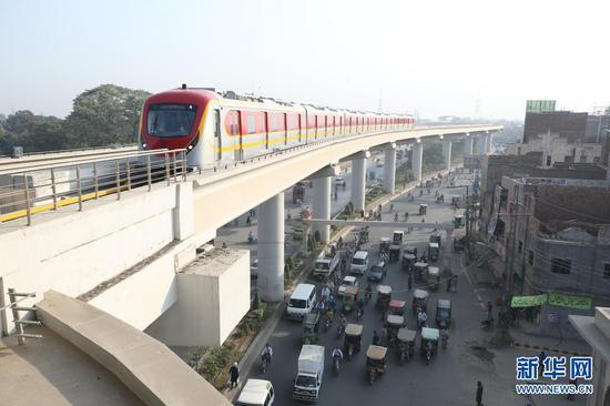 """在巴基斯坦拉合尔市,一辆橙线地铁列车准备进站(2020年10月26日摄)。当日,巴基斯坦首条地铁——拉合尔橙线迎来首批乘客,标志着巴基斯坦步入""""地铁时代""""。新华社记者刘天摄"""