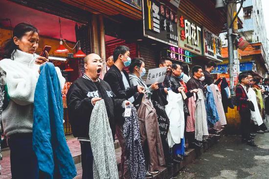 2021年 3月3日,元宵节之后的工作日,广州康乐村街头,制衣厂的老板们排成一列,手里拿着样板招募前来务工人员。图/人民视觉