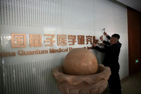 """2021年4月23日,执法人员依法拆除""""中国国学院大学国医药生命科学院量子医学研究院""""标识。"""