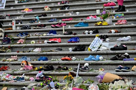 5月30日,在加拿大温哥华,人们摆放鲜花、鞋子等物品,悼念不列颠哥伦比亚省坎卢普斯市一所原住民寄宿学校的死者。新华社发(宋伟仁摄)