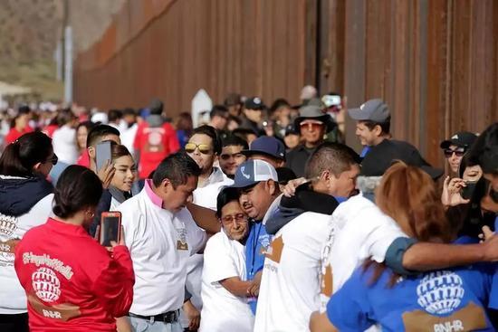 2018年10月13日,在墨西哥北部边境城市华雷斯附近的美墨边境,分隔两国的侨民和亲人团圆。新华社/路透