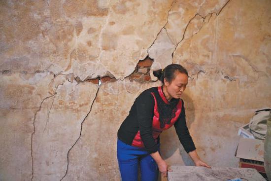 ▲村民王仕杰家,4米长呈对角线状的一处位于中寨断裂带的房屋墙体开裂严重。 裂缝贯穿墙体,裂缝最宽处有3厘米,透光。