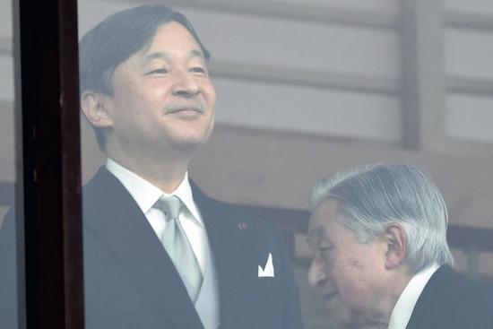 2018年12月23日,日本首都东京,明仁天皇(右)从皇太子德仁身后走过。当日是明仁天皇85岁生日。图/新华