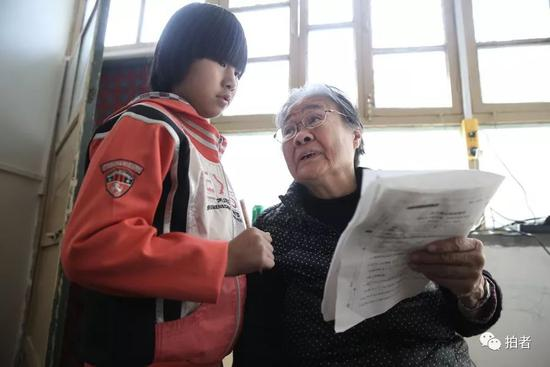 """""""小课桌""""上,严敏文正在解答小女孩儿提出的问题。新京报记者尹亚飞摄"""