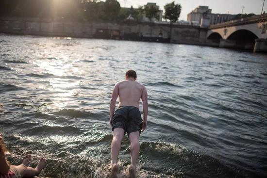 7月1日,在法国首都巴黎的塞纳河畔,一名男子纵身跳入水中。新华社/美联