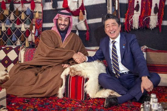 安倍与沙特王储握手(时事通信社)