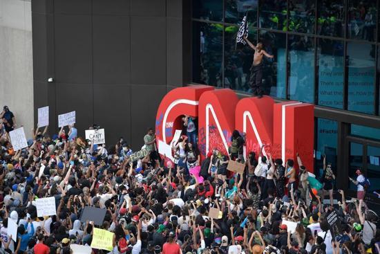 (图说:示威者在CNN总部外观的抗议游走中在徽标上绘画。图源/AP)