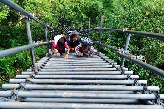 """2017年11月5日,悬崖村的孩子们放学后攀爬天梯回家往。""""钢梯上的肄业梦""""让这群孩子天晴下雨有了坦然通道。"""