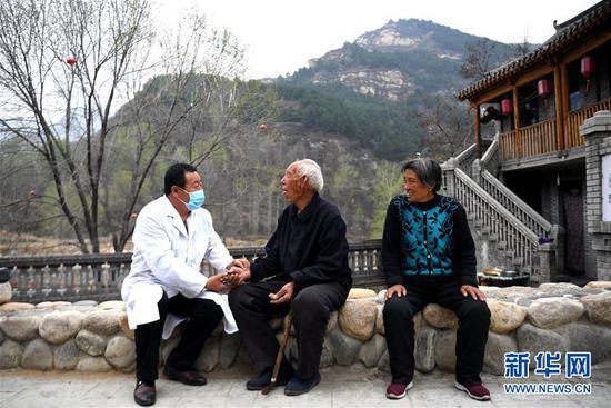 在河北省阜平县骆驼湾村,村医霍建国为村民把脉(2020年4月15日摄)。 新华社记者 王晓 摄