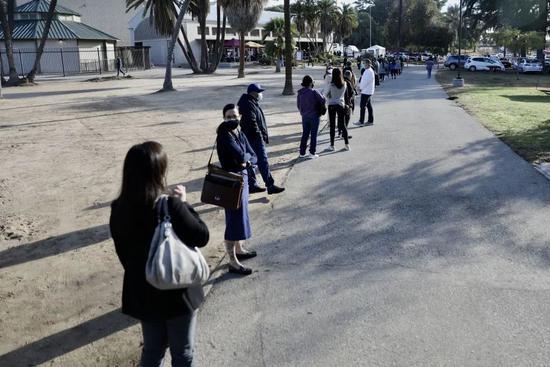 ▲1月6日,在美国加州洛杉矶的一处新冠疫苗接种站,医护人员排队等待接种新冠疫苗。(新华社发)