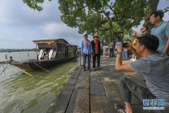 7月1日,两名老党员在浙江嘉兴南湖湖心岛停泊的南湖红船旁拍照留影。新华社记者 徐昱 摄