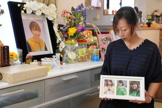 大本萌景的母亲在看女儿生前照片(图片来源:朝日新闻)