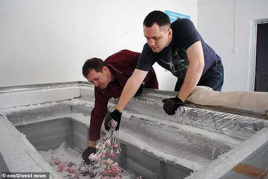 支属将鲜花放入尤里·皮丘金的棺材中,随后他的遗体被运去蓄积的地方。图片来源:east2west news
