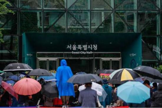 7月13日,在韩国首尔市当局大楼前,市民们冒雨告别已故首尔市长朴元淳。新华社记者 王婧嫱 摄