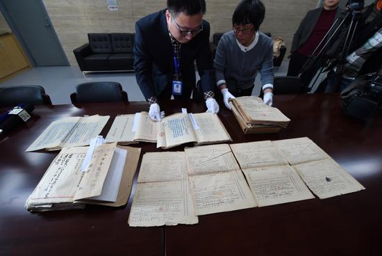 南京市档案馆人员展示相关档案。(2015年记者孙参摄)