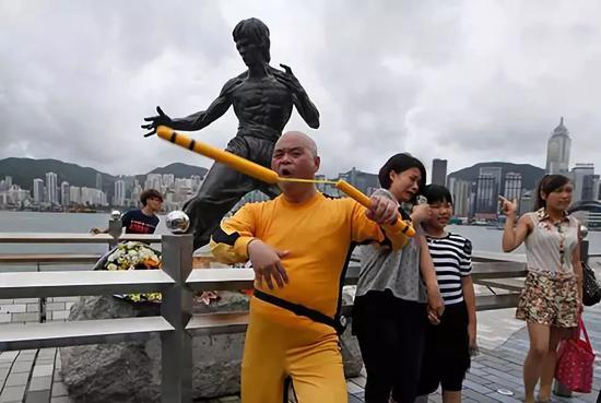 一位日本粉丝在李幼龙雕塑前展现双节棍技能。(美联社)