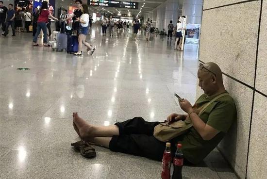 樊建川在火车站席地而坐