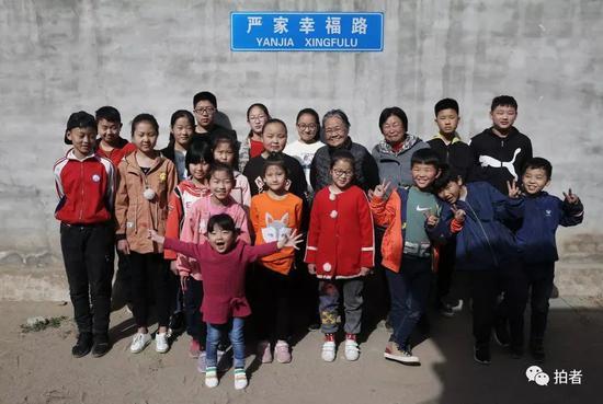 """4月5日,河北涞水西官庄村,严敏文(居中戴眼镜老人)和一名志愿者(严左手边)与""""小课桌""""的孩子们一起合影。新京报记者尹亚飞摄"""
