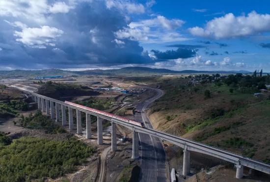 2017年5月12日,列车从肯尼亚蒙内铁路沿线的马泽拉斯铁路大桥上驶过。由中国承建的蒙巴萨-内罗毕标轨铁路(蒙内铁路)全长约480公里,是肯尼亚自独立以来最大的基础设施工程。新华社记者 陈诚 摄
