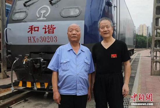 曹均宽(左)、李钰明在新式祥和大功率电力机车前相符影。宝鸡机车检修厂供图