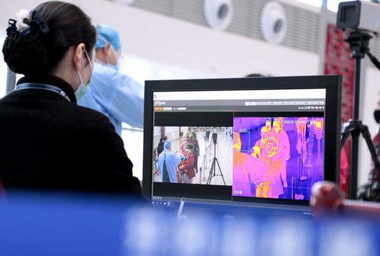 江西井冈山机场工作人员利用红外人体热成像测温系统对乘客进行体温监测(2月10日摄)。新华社发(司马天民 摄)