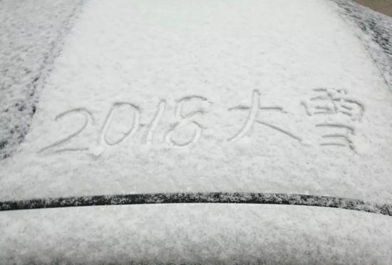 """△7日,江苏无锡,市民在积雪上写着""""2018大雪""""字样。(图自视觉中国)"""