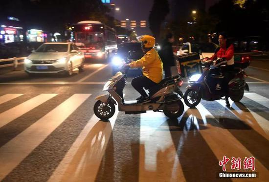 资料图:外卖员安兴在送餐的路上。中新社记者 吕明 摄