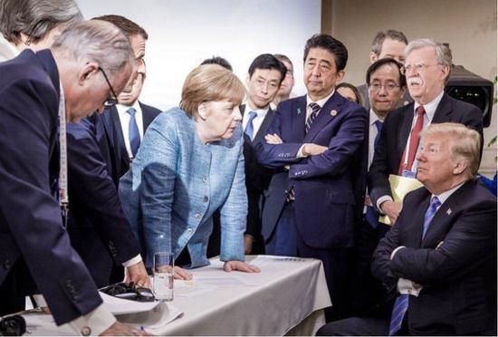 """(图:2018年6月,在七国集团首脑会议(G7)上,美国向它的欧美盟友挥起了关税大棒,造成了美国与其他六国的""""严重分歧""""。这张现场新闻照片,被网友戏称""""六大门派围攻光明顶""""。)"""