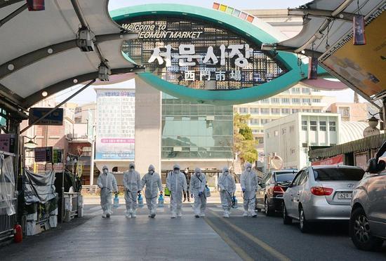 ↑2月23日,在韓國大邱,受疫情影響而臨時休業的商家工作人員在西門市場進行防疫消毒。新華社發
