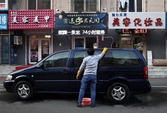 12月1日,辣椒在店门口擦洗本身的车,第二天要当出殡的头车。