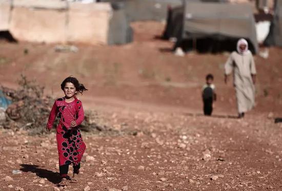 资料图片:9月2日,在叙利亚伊德利卜省的一个村庄,一名儿童走在难民营里。(新华社)