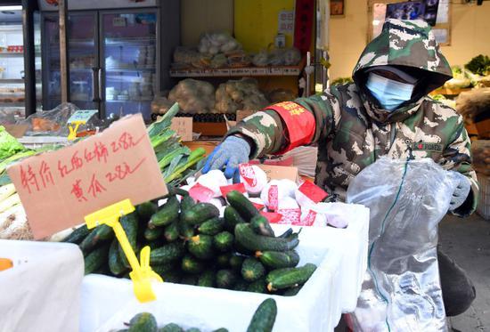 1月16日,在北京市海淀区学院路街道石油大院社区便民菜站,工作人员在码放蔬菜。新华社记者 任超 摄
