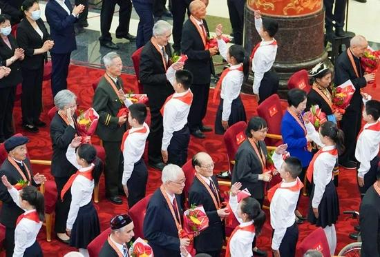 """▲2021年6月29日,""""七一勋章""""颁授仪式在人民大会堂隆重举行。少先队员向勋章获得者献花,敬礼致意。"""