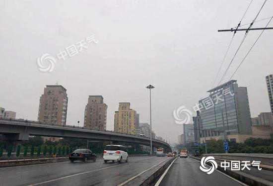 今晨,北京天空阴沉,雨水纷飞。(图/王晓)