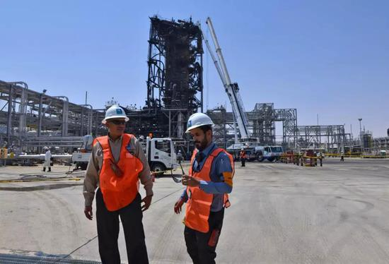 9月20日,在沙特胡赖斯,沙特国家石油公司员工在遭无人机袭击的石油设施附近工作。新华社/法新