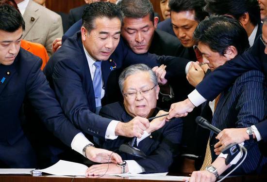 日本执政党与在野党成员夺取麦克风(图源:美联社)