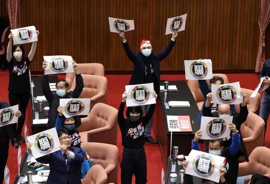 """国民党""""立委""""24日手持标语要民进党不要再欺骗民众。(图片来源:台湾《联合报》)"""