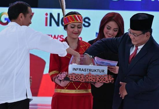 印尼总统佐科(左)与其对手普拉博沃(右)在第二场电视辩论中,就基础设施课题抽选问答题。(图源:法新社)