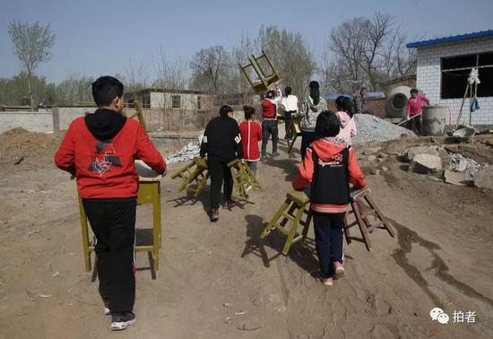 新教室即将竣工,孩子们将爱心人士捐赠的课桌椅子从老址搬往新址。新京报记者尹亚飞摄