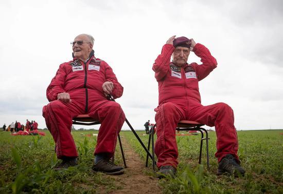 哈里?里德(左)和约翰?赫顿(右)跳伞完毕后坐下休息