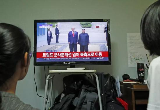 6月30日,韩国首尔市民在家里收看朝鲜最高领导人金正恩(屏幕右侧)与美国总统特朗普会面的电视直播。新华社记者王婧嫱摄