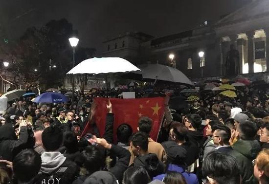 """16日晚,澳大利亚墨尔本州立图书馆前,留学生们""""雨中护旗"""""""