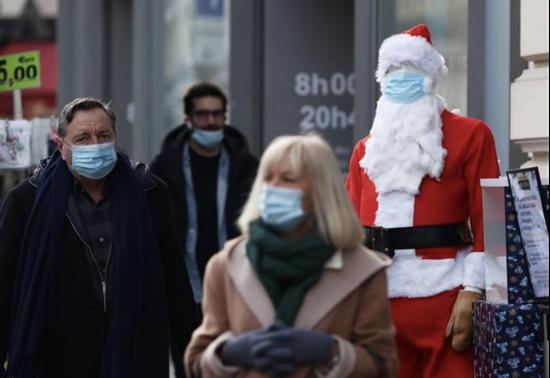 巴黎一家超市门前,圣诞老人模型也戴上了口罩 图:新华社